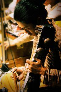 サーランギ奏者 オカダケンシン2009年、聖地ベナレスにてShivendra Mishra氏、Fiyaz Ali Khan氏の元、弓奏楽器サーランギの修行を始める。 以降毎年渡印。2014年よりデリーにてMoradabad流派の巨匠Ustad Ghulam Sabir Khan氏に師事。 北インド古典音楽をはじめ、様々なジャンルのアーティストとのセッションも行いながら田畑を営み薪で暮らす。岡山在住。